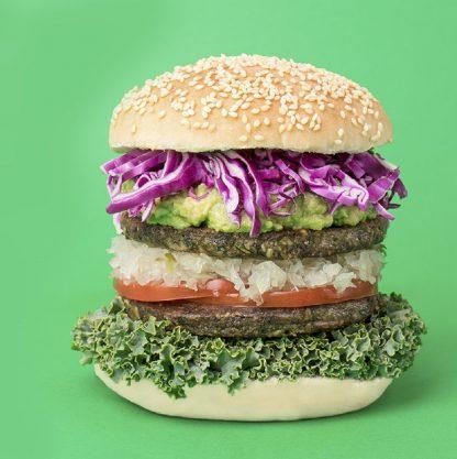 Apetitoso sandwich de hamburgesa de poroto negro con repollo morado, palta, cebolla, romate y lechuga