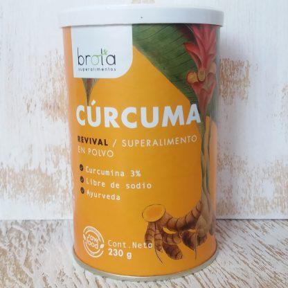Foto del frente del tarro de cartón con tapa de plástico, hermético que contiene la cúrcuma. Se observa la planta con los rizomas de la raíz, tallo, hojas y flor de hermosos pétalos rosados