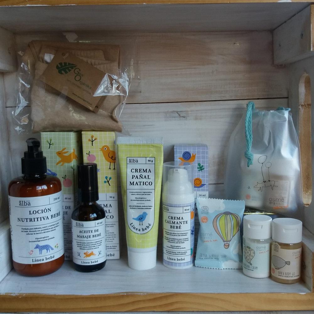 Estantería de la tienda con artículos para bebés: crema pañal matico, loción nutritiva, aceite de masaje, kit de viaje con jabón, champú y loción y pantys de algodón pima